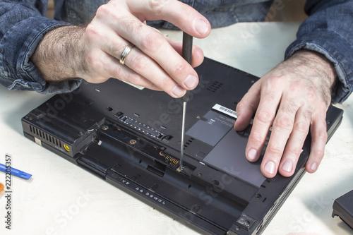 Obraz Rozkręcanie obudowy laptopa w serwisie komputerowym. - fototapety do salonu
