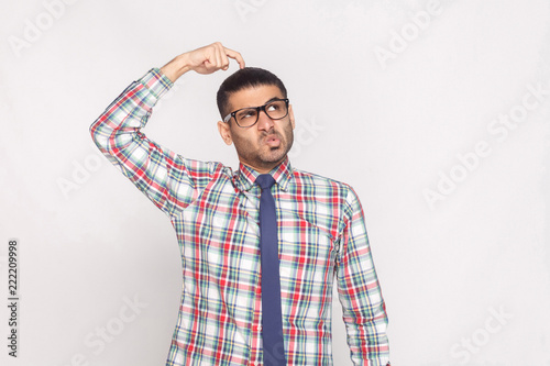portrait of thoughtful handsome bearded businessman in colorful checkered shirt, blue tie and eyeglasses standing and looking away with funny face Wallpaper Mural