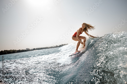 Active blonde girl standing on the wakeboard on the lake