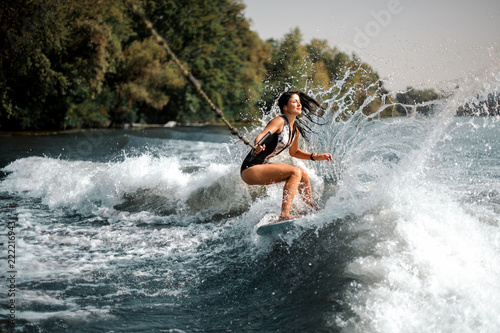 Smiling brunette girl riding on the wakeboard holding a rope