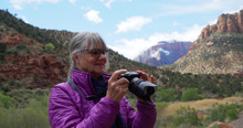 Senior Female Photographer Taking Pictures Of Sandstone Canyon In Zion Utah