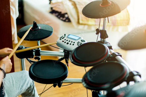 Asian girl put black tshirt and headphone learning and play electronic drum wood Fototapeta