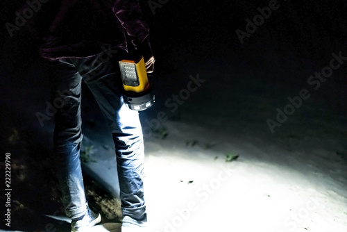 Obraz close up hand holding electric torch flashlight in dark nature forest outdoor standing on sand a - fototapety do salonu