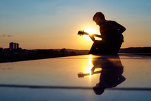 Young Man Playing Electric Guitar In Sunset.