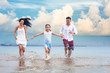 Happy asian family - father, mother, kid hold hands and run together with fun along daylight sea beach. Travel, active lifestyle, parents with children on tropical summer vacations..