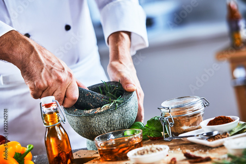 Worker mixing spices with mortar and pestle