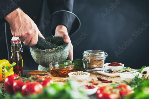 Chef grinding herbs in a pestle and mortar