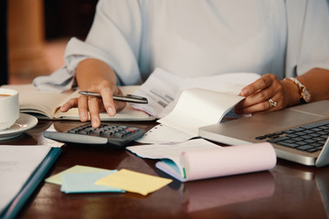 Fototapeta Hands of female entrepreneur working with bills and documents