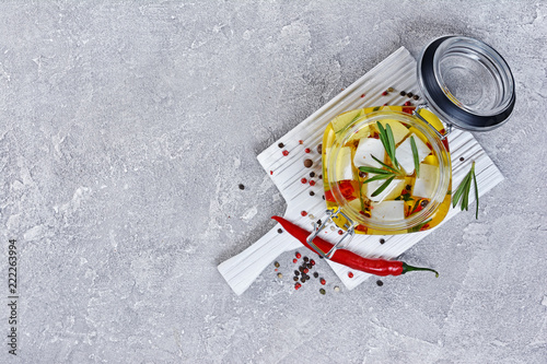 Top view of marinated feta cheese with olive oil and spice of red chili pepper and rosemary in glass jar on white wooden board