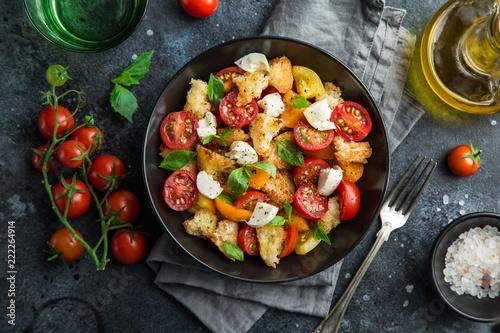 Fotografía panzanella, traditional italian tomato, mozzarella and bread salad in black bowl