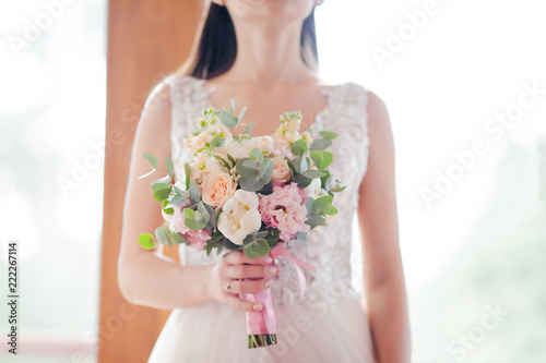 Wedding bouquet of white peony and pink roses. Lots of greenery.
