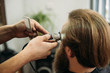 Bearded man having a haircut with a hair clippers. Closeup view with shallow depth of field