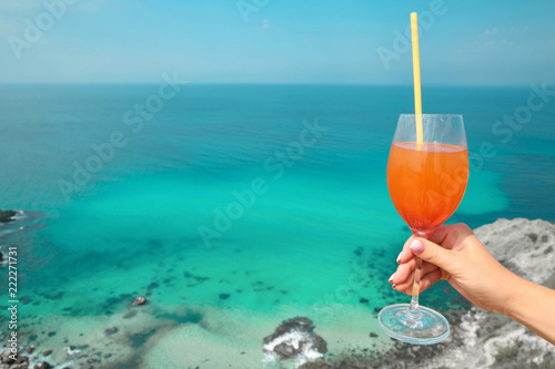 Summer Cheers! Cropped image of Hand with orange coctail glass over turquoise lagoon exotic bay. Lifestyle summertime vacation concept. Black sea coast, cape Fiolent, Crimea.