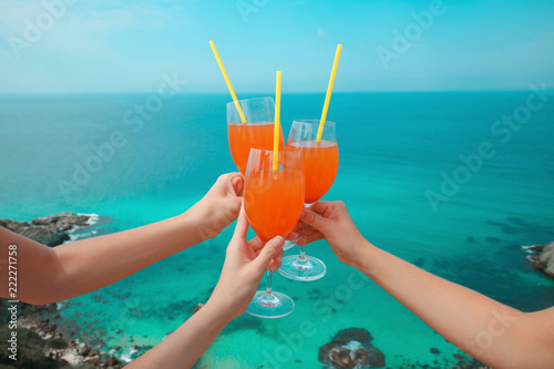 Spoed Foto op Canvas Cocktail Summer party Cheers! Cropped image Hands of three people holding orange coctail glass with Straw over turquoise lagoon exotic bay. Lifestyle summer vacations concept. Black sea coast, Crimea.