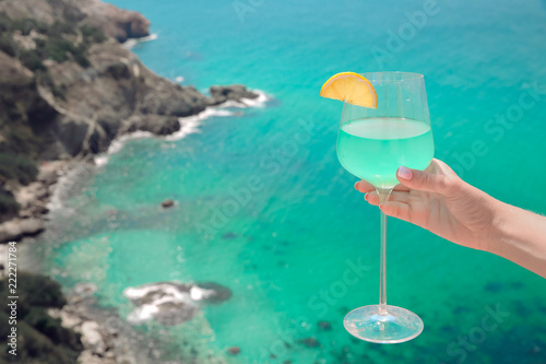 Summer Cheers! Cropped image of Hand with blue curacao cocktail glass over turquoise lagoon exotic bay. Lifestyle summertime vacation concept. Black sea coast, Crimea.