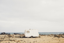 Really Alternative Lifestyle In Contact With The Nature And Yourself Living In The Middle Of Nowhere With A Little Tiny House Caravan Parked On The Coast With Ocean Waves View. Independence And Wild.