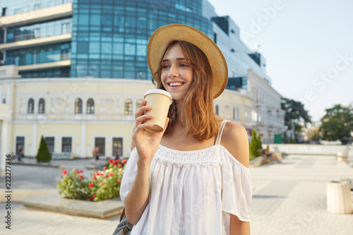 578cd133f Outdoor portrait of happy cute young woman wears stylish summer hat and white  dress, feels relaxed, smiling and drinking takeaway coffee on the street .