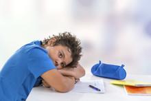 Overwhelmed Schoolboy. Bored And Tired Teenage Boy Doing Homework On Desk In His Room,seems Sleepinp