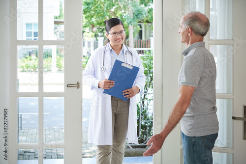Elderly man opening door to smiling doctor making visit at home Fototapete