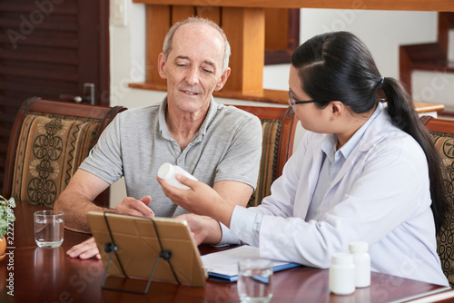 Photo  Woman at table with tablet and papers and showing pills in jar to senior patient