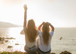 Two blond girls sitting on a cliff of island observing the horizon and raise his arms in the air