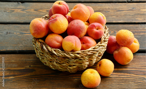 Fresh Apricot in the basket on wooden background.