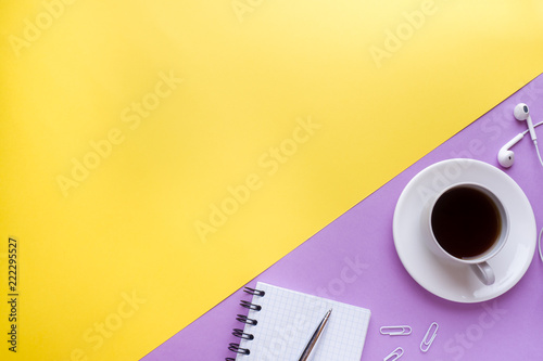 Leinwand Poster  Notepad for text and Cup of coffee on yellow pink table with copy space