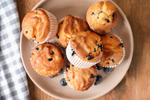 Plate With Tasty Blueberry Muffins On Wooden Table