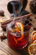 Glass of delicious hot mulled wine on wooden table