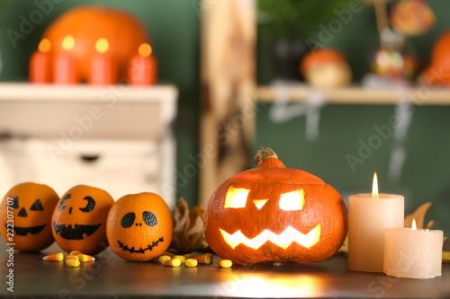 Table with burning candles and pumpkin prepared for