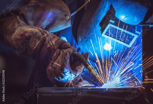 Fotografie, Obraz Industrial Worker at the factory welding steel structure