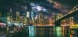 New York City Brooklyn Bridge and Manhattan skyline illuminated at night with full moon overhead.