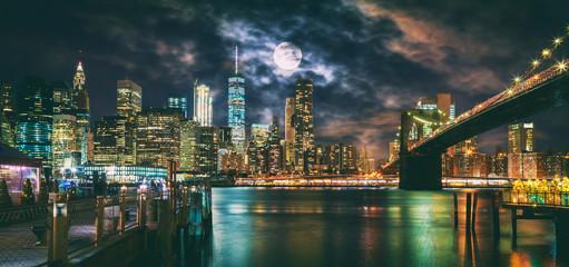 Fototapeta New York City Brooklyn Bridge and Manhattan skyline illuminated at night with full moon overhead.