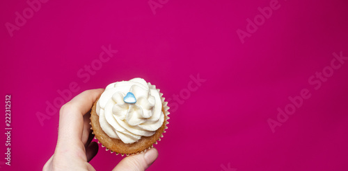 Fotografering  Cupcake with hand on pink background