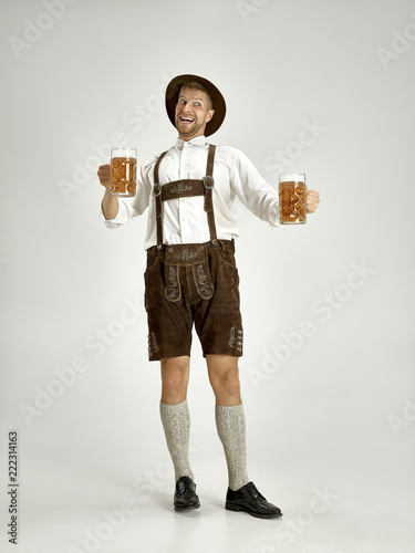 Leinwand Poster Portrait of Oktoberfest young man in hat, wearing a traditional Bavarian clothes standing with beer at full-length at studio