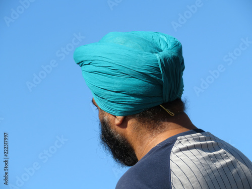 Obraz na płótnie Bearded Indian sikh in a cyan turban on a background of clear blue sky, rear view