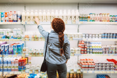 Carta da parati Young woman in striped shirt from back choosing dairy products in supermarket