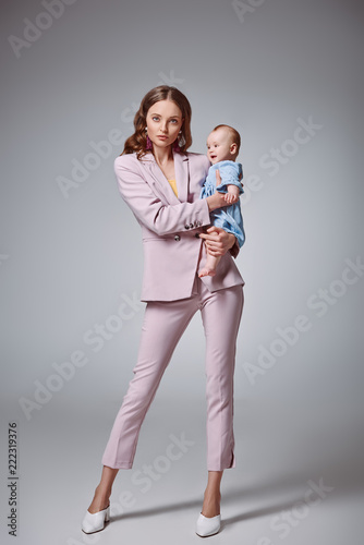 Foto full length view of stylish young mother holding adorable infant daughter and lo