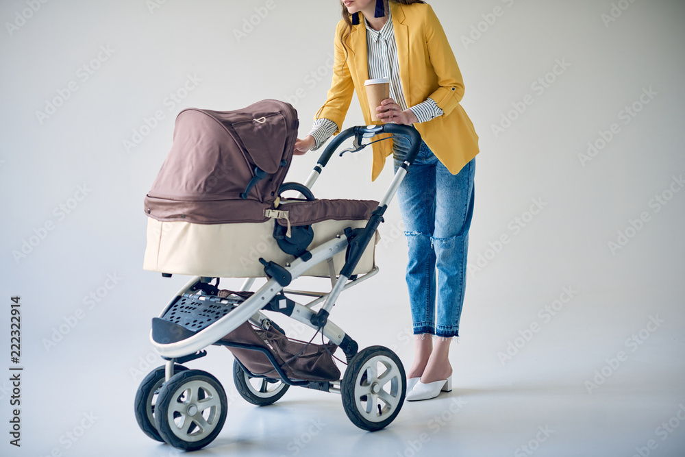 Fototapety, obrazy: cropped shot of fashionable woman holding disposable coffee cup and standing with baby carriage on grey