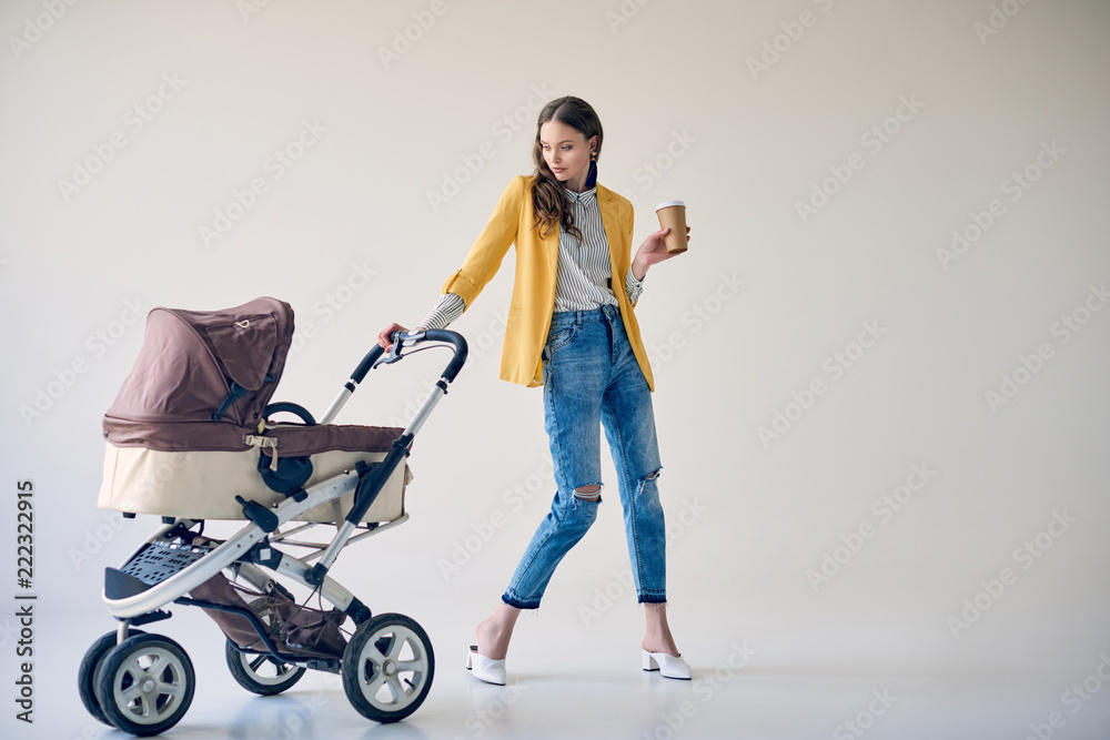 Fototapety, obrazy: stylish young woman holding disposable coffee cup and looking at baby stroller on grey