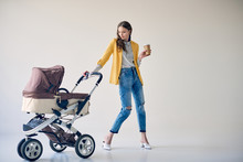 Stylish Young Woman Holding Disposable Coffee Cup And Looking At Baby Stroller On Grey