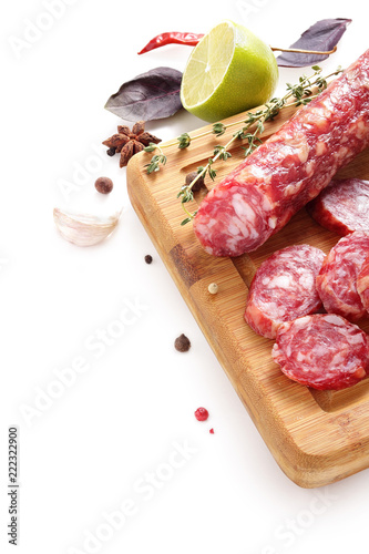 Fotografie, Obraz  still-life with smoked sausage, salami bay leaf and onion on a wooden aged textu