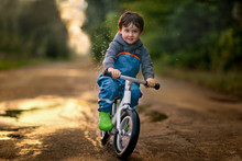 Boy Riding Bicycle Through A Puddle