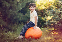 Boy Sitting On The Big Pumpkin