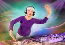 Cheerful Elderly Woman Plays Music On A DJ Console. A Disco Party In A Nightclub For Young And Overweight People. Age Of Health, Leisure, Entertainment In Retirement