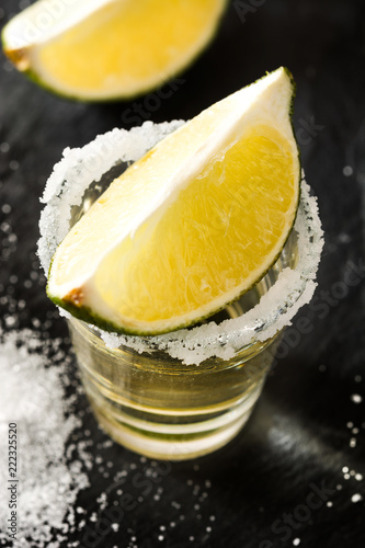 Mexican Gold tequila with lime and salt on black background. Close up
