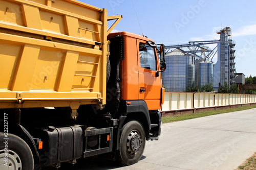 orange truck on the territory of grain storage in sunny weather harvesting Slika na platnu