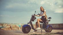 Young Woman Riding Electro Sco...