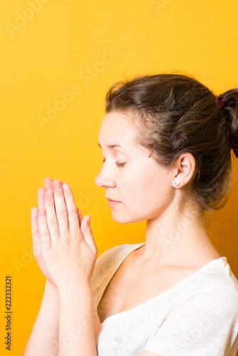 Fotografia  brunette a bright girl prays in harmony