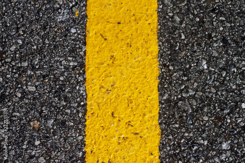 Fotografiet  Close up of yellow line on street asphalt.